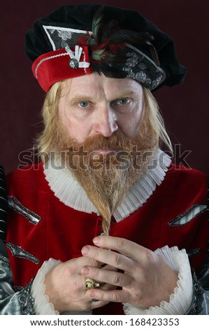 close-up portrait of a man with a beard and mustache in a medieval suit and hat studio on a burgundy background - stock photo