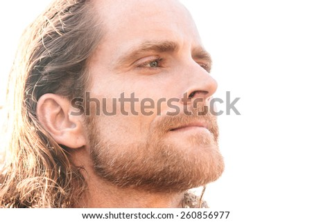 Close up portrait of a man with beard and long hair looking far away - stock photo