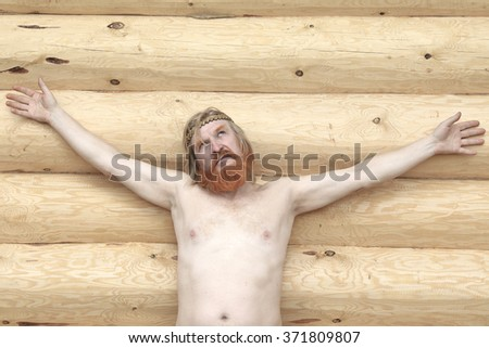 close-up portrait of a man with naked torso against the backdrop of a new log house in sunny spring day  - stock photo