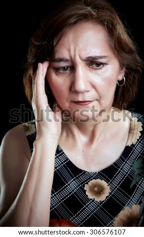 Close-up portrait of a middle aged woman with headache, massaging forehead with her right hand. Black background. - stock photo