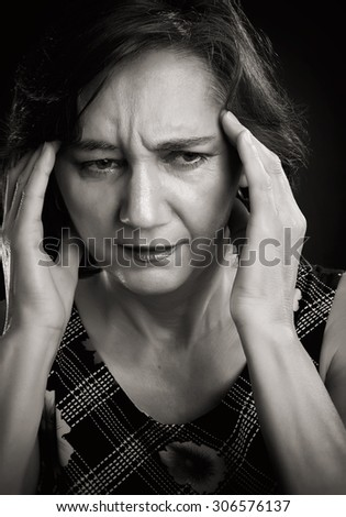Close-up portrait of a middle aged woman with headache, massaging her forehead with both hands. Sepia picture, isolated on black. - stock photo
