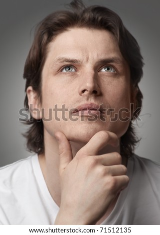 Close-up portrait of a pensive handsome man looking up against white background - stock photo