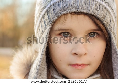 Close-up portrait of a pretty girl with blue eyes in gray knit hat - stock photo