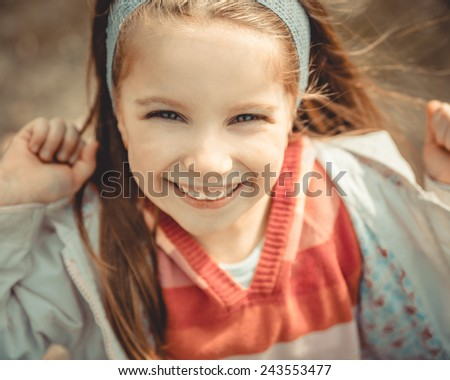 Close-up portrait of a pretty smiling liitle girl - stock photo