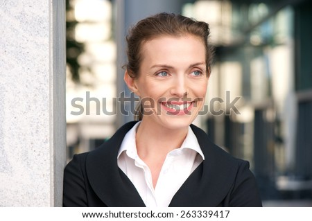Close up portrait of a professional business woman smiling outdoors - stock photo