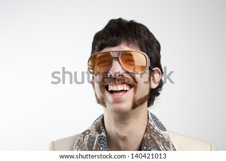 Close up portrait of a retro man in a 1970s leisure suit and sunglasses smiling and laughing - stock photo