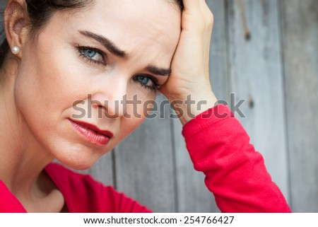 Close-up portrait of a  sad, depressed and lonely woman sitting down. - stock photo