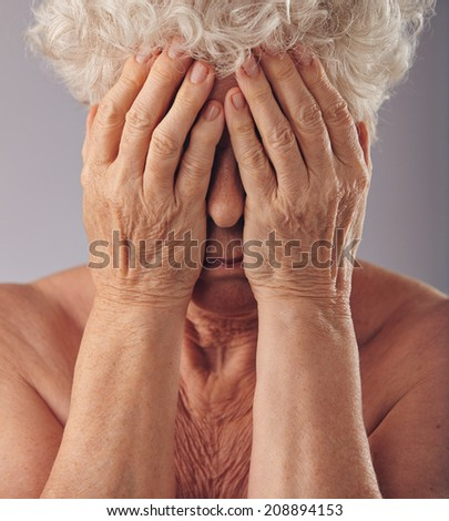 Close-up portrait of a sad looking senior woman with her head in her hands against grey background. Upset old woman covering her face. - stock photo