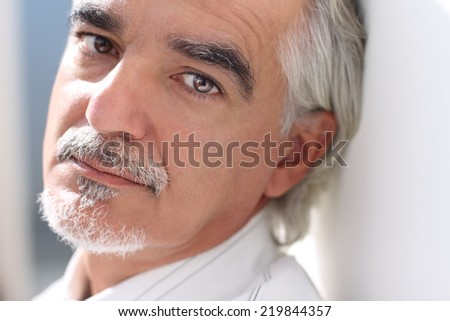 Close-up portrait of a senior businessman  looking at camera thoughtfully - stock photo
