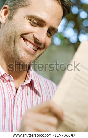 Close up portrait of a senior businessman reading a financial newspaper while sitting in the city, smiling. - stock photo