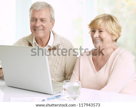 Close-up portrait of a senior couple in front of laptop - stock photo