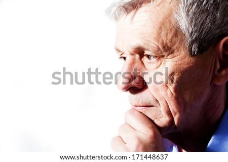 close-up portrait of a senior man thinking - stock photo
