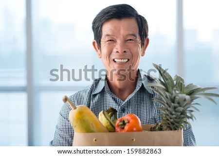 Close-up portrait of a senior man with a bag of fruits smiling and looking at camera - stock photo