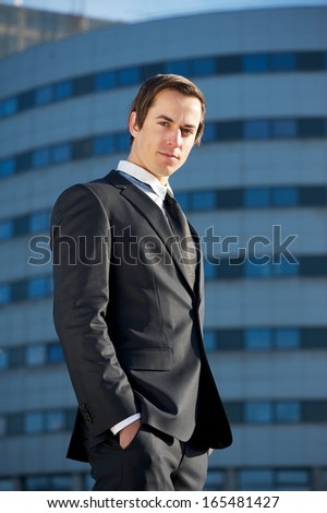 Close up portrait of a serious businessman standing outside office building - stock photo