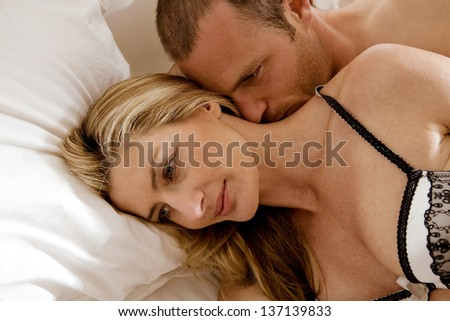 Close up portrait of a sexy couple laying down in bed, relaxing and kissing and having a romantic moment. - stock photo