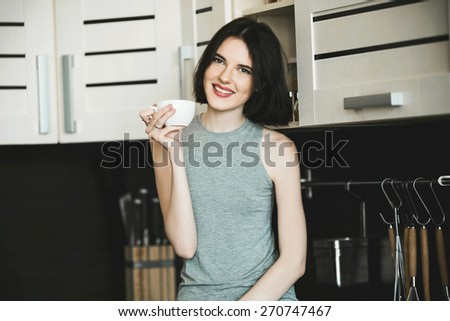 Close up portrait of a slim beautiful woman housewife standing in kitchen having rest after cooking - stock photo