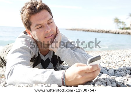 "Close up portrait of a smart man laying down on the shore of a white pebble beach being thoughtful while using a ""smart phone"". - stock photo"