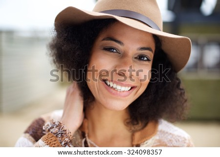 Close up portrait of a smiling african american fashion model with hat - stock photo
