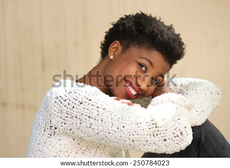 Close up portrait of a smiling african american woman sitting outdoors - stock photo