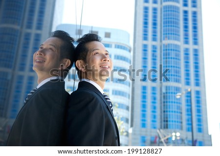 Close up portrait of a smiling asian businessman in the city - stock photo
