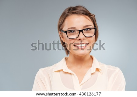 Close-up portrait of a smiling beautiful girl isolated on the gray background - stock photo