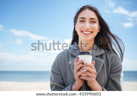 Close-up portrait of a smiling cheerful girl holding takeaway cup at the seaside - stock photo