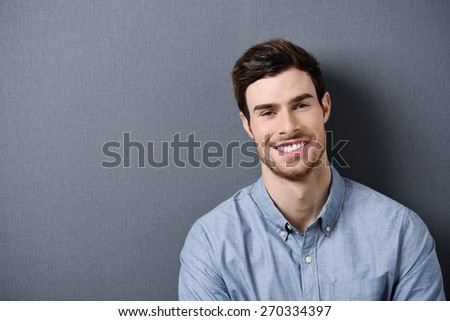 Close up Portrait of a Smiling Handsome Young Man Looking at the Camera, Isolated on Gray Background with Texts Space at the Left Side. - stock photo