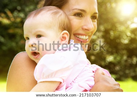 Close up portrait of a smiling mother holding cute baby - stock photo