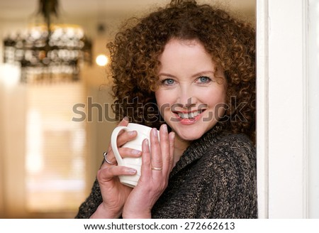 Close up portrait of a smiling older woman holding cup of tea at home - stock photo