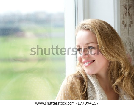 Close up portrait of a smiling woman looking outside through window - stock photo