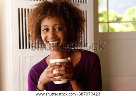 Close up portrait of a smiling young african american woman drinking coffee - stock photo