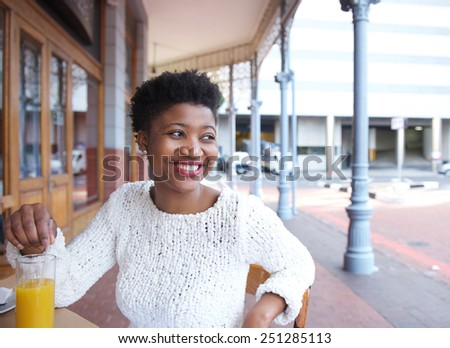 Close up portrait of a smiling young african american woman sitting at outdoor restaurant  - stock photo