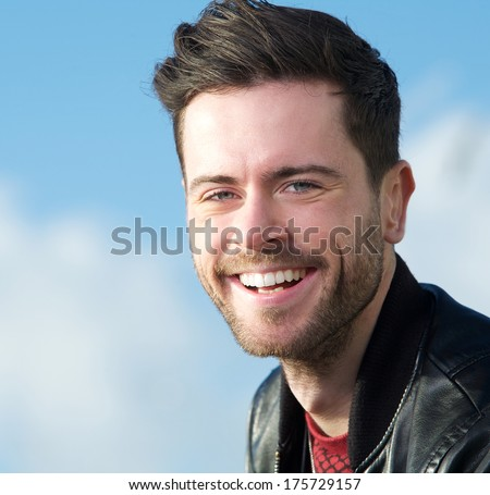 Close up portrait of a smiling young man posing outside - stock photo