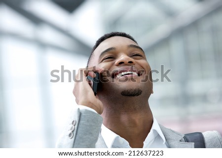 Close up portrait of a smiling young man talking on mobile phone - stock photo
