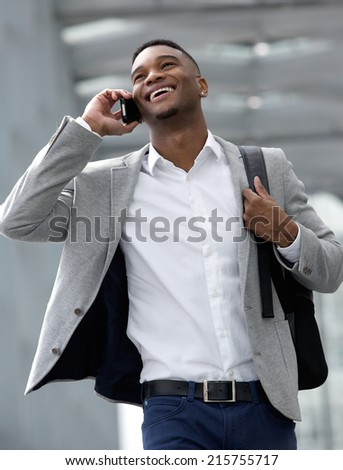Close up portrait of a smiling young man walking and talking on mobile phone - stock photo