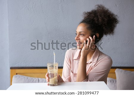 Close up portrait of a smiling young woman sitting at restaurant talking on mobile phone - stock photo