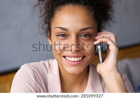 Close up portrait of a smiling young woman talking on mobile phone - stock photo