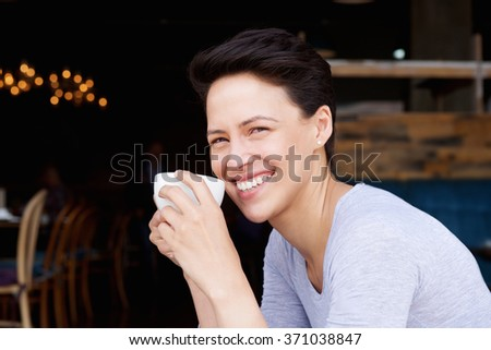Close up portrait of a smiling young woman with cup of coffee  - stock photo