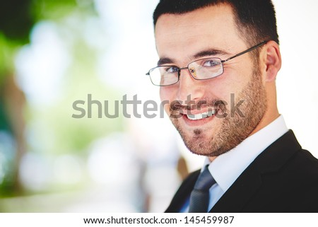 Close-up portrait of a successful business guy smiling ambitiously - stock photo