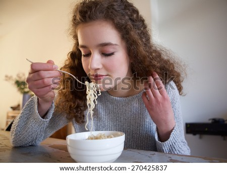 Close up portrait of a teenage girl eating noodles at home - stock photo