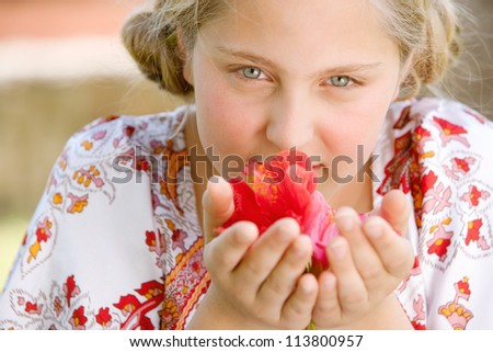 Close up portrait of a teenage girl smelling hibiscus flowers, smiling. - stock photo