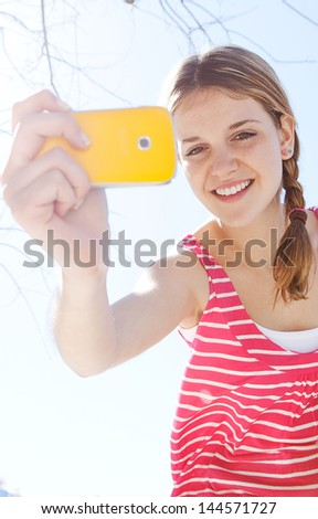 Close up portrait of a teenager girl using her smartphone to take pictures against a blue sky during a sunny day, smiling at the camera and having fun. - stock photo