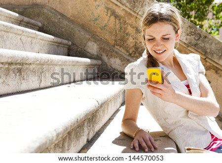 Close up portrait of a teenager student using her smart phone while sitting down at a college stone steps during a sunny day, smiling. - stock photo