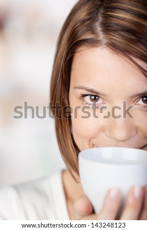Close-up portrait of a woman holding a coffee mug close to her face. - stock photo