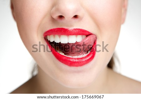 Close up portrait of a woman licking teeth with tongue - stock photo
