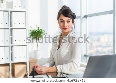 Close-up portrait of a woman sitting in modern loft office, smiling, looking at camera. Young confident female business worker ready for the work day. - stock photo