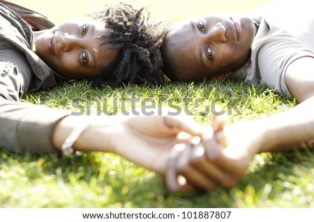 Close up portrait of a young african american couple laying down on green grass in the city, on a sunny day. - stock photo