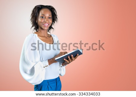 Close-up portrait of a young african woman with a book - stock photo