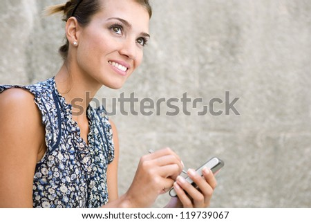 Close up portrait of a young attractive businesswoman using digital technology against a stone wall, outdoors. - stock photo