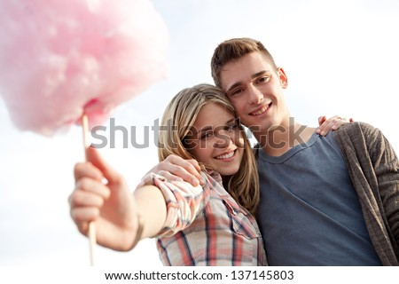Close up portrait of a young attractive couple in a fun fair, holding a cotton candy sweet towards the camera, smiling against a blue sky. - stock photo